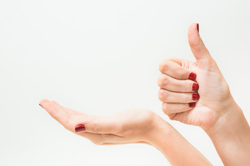 Young girl with beautiful red manicure holding hand as if showing something virtual and invisible on palm. Other female hand in gesture with thumb up. Close up of hands isolated on white background.