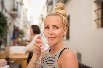 Woman drinking water at sidewalk cafe, Altea, Alicante Province, Spain