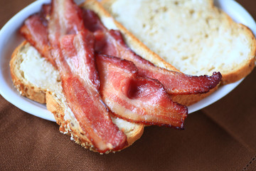 Bacon slices on buttered whole-grain bread