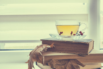 Cup of hot tea, old books, autumn leaves and berries on the window. Autumn still life. Coloring and processing photo.