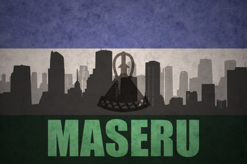abstract silhouette of the city with text Maseru at the vintage lesotho flag