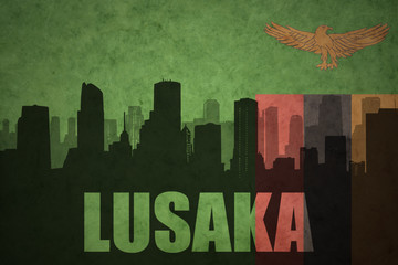 abstract silhouette of the city with text Lusaka at the vintage zambian flag