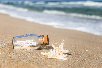 message in a bottle and starfish/bottle with a message happy new year on sandy beach in Florida.