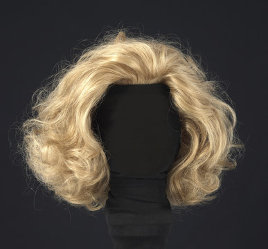 blonde feminine wig on black background and textile mannequin.