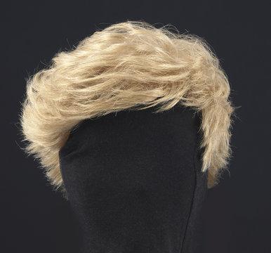 blonde feminine wig on black background and textile mannequin.