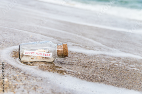 message in a bottlebottle with a message happy new year on sandy beach in