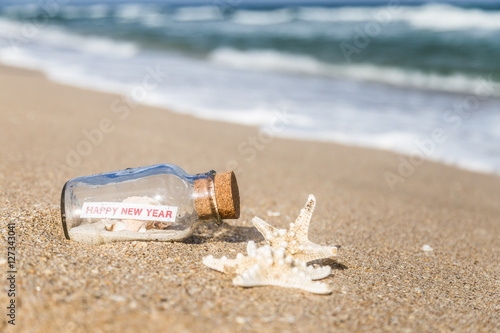 message in a bottle and starfishbottle with a message happy new year on sandy