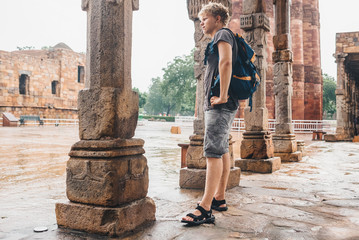 Young tourist man waits when intense rain stop on the yard of Qu