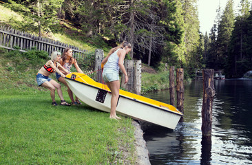 Three adult female friends launching rowing boat into lake, Sattelbergalm, Tirol, Austria