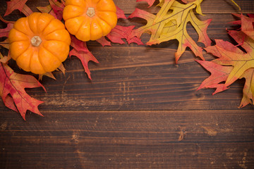Autumn leaves  and pumpkins on a wooden background forming a bor