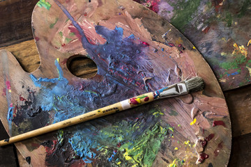 Used Artist paint brush and palette of colorful oil paint on wooden background   for drawing and painting