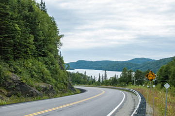 curved road with large lake and mountains in distance