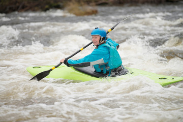 Young female kayaker paddling River Dee rapids