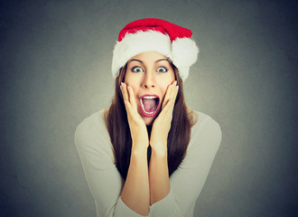 Surprised excited happy woman wearing red santa claus hat looking shocked