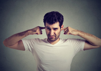 displeased man plugging ears with fingers doesn't want to listen