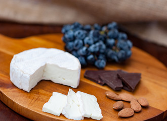 Brie camembert cheese wedge slices almonds, dark chocolate pieces dark blue purple black concord grapes on wooden chopping cheese board dark brown wooden table brown burlap background copy space