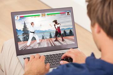 Man Playing Videogame On Laptop
