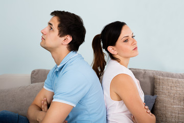 Close Up Of Sad Couple Sitting Back To Back