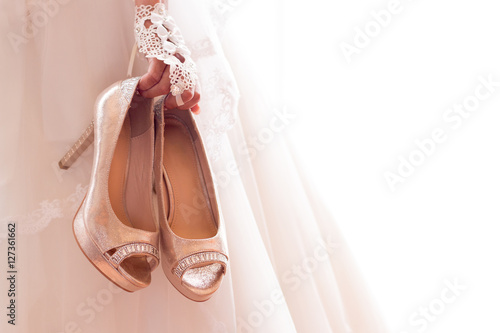 """""""Beautiful bride in white wedding dress is holding shoes ..."""
