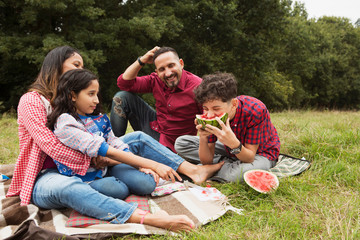 Family sitting outdoors, on picnic blanket, son eating watermelon