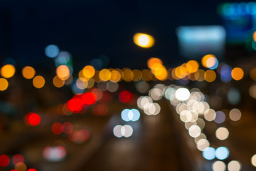 blurred photo of car on the road with bokeh background of city street night light.