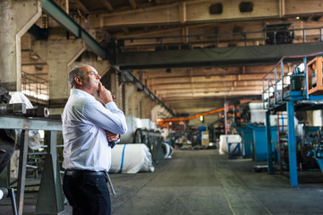 Man in tyre manufacturing point, hand on chin, looking away thinking, Ballenstedt, Germany
