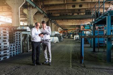 Colleagues conferring in tyre manufacturing plant, Ballenstedt, Germany