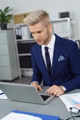 junger geschäftsmann arbeitet konzentriert am laptop