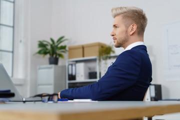 mann im büro sitzt nachdenklich am schreibtisch