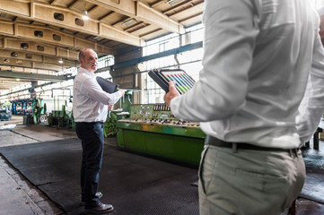 Colleagues holding digital tablets in tyre manufacturing plant, Ballenstedt, Germany
