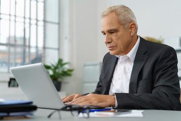 erfahrener älterer geschäftsmann arbeitet am laptop