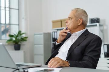nachdenklicher älterer unternehmer in seinem betrieb