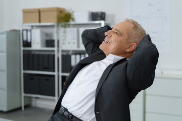 älterer geschäftsmann lehnt sich entspannt zurück