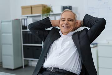 erfolgreicher älterer geschäftsmann lehnt sich entspannt zurück