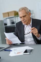 älterer geschäftsmann liest einen brief im büro