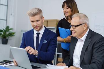 team im unternehmen schaut gemeinsam auf laptop