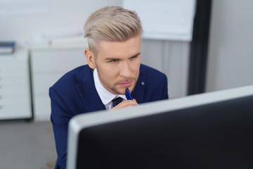 nachdenklicher mann im büro schaut aus seinen computer