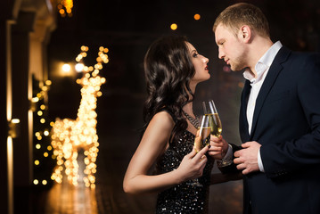 Elegant couple toasting the New Year with champagne  and joy as they clink glasses against strings of twinkling party lights