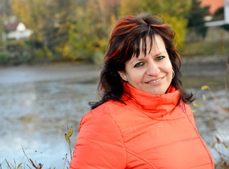 Portrait of smilling middle aged ordinary caucasian woman with long dark hair and red jacket in park.