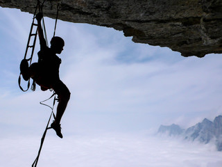a climber aid climbing a large roof in the Swiss Alps near the Walensee