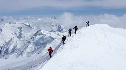 a mountain guide and clients on an exposed summit ridge during a winter ascent in the Austrian Alps
