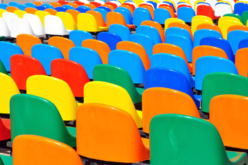 Rows of colorful plastic chairs on the back side. Yellow, red, orange, green, blue colors.