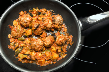 Meatballs with vegetables on a frying pan