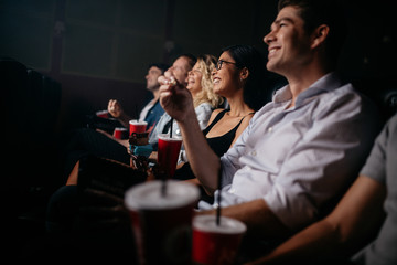 Group of people in theater with popcorn and drinks