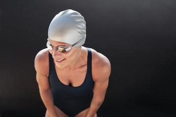 Female swimmer on black background