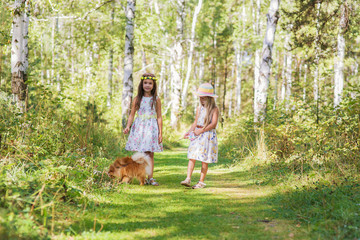 two girls girlfriend walking in the woods with her beloved pet Spitz