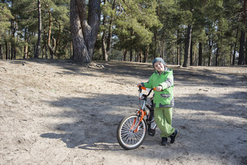 Happy baby funny little boy standing with his bicycle in a pine