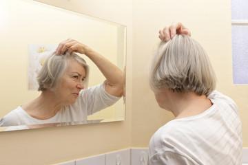 Senior woman examining hair loss