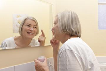Happy mature woman moisturizer mirror