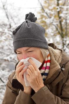 senior woman blowing nose winter
